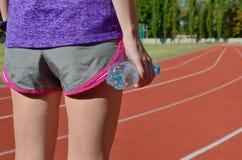 Aptidão e conceito running, vista traseira do corredor fêmea na trilha do estádio com a garrafa da água Imagens de Stock