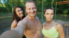 Aptidão, esporte, amizade, tecnologia e conceito saudável do estilo de vida - grupo de amigos felizes que tomam o selfie fora filme