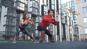 Aptidão, esporte, exercício e conceito saudável do estilo de vida - homem e mulher que fazem ocupas fora na cidade video estoque