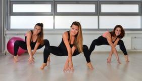 Aptidão, esporte, exercitando o estilo de vida - grupo de mulheres felizes nos bodysuits que dançam no gym imagens de stock royalty free