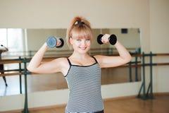Aptidão, esporte, exercitando o estilo de vida - mulher atrativa que faz exercícios do levantamento de peso no gym imagem de stock royalty free