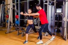 Aptidão, esporte, treinamento e conceito dos povos - mulher de ajuda do instrutor pessoal que trabalha com no gym fotografia de stock