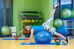 Aptidão, esporte, treinamento, gym e conceito do estilo de vida - jovem mulher que faz o exercício na bola da aptidão imagens de stock royalty free