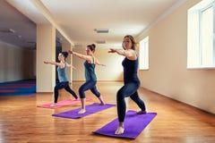 Aptidão, esporte, treinamento, ioga e conceito dos povos - mulher caucasiano que estica o pé na esteira no gym Grupo de fazer fêm foto de stock royalty free