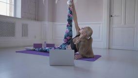 Aptidão home Fazer do treinamento da jovem mulher Músculos e junções do estiramento Vídeos de observação no Internet no portátil filme