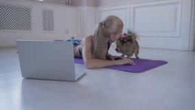 Aptidão home Jovem mulher durante o exercício e jogos com o Spitz pequeno do cão Vídeos de observação no Internet no portátil filme