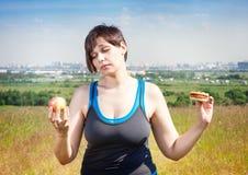 Aptidão mais a mulher do tamanho que faz a escolha entre saudável e a sucata f Foto de Stock