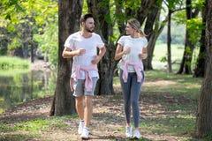 aptidão nova dos pares no sportswear que corre junto no parque homem e mulher do esporte que movimentam-se fora na natureza exerc fotos de stock royalty free