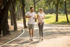 aptidão nova dos pares no sportswear que corre junto no parque homem e mulher do esporte que movimentam-se fora na natureza exerc imagem de stock royalty free