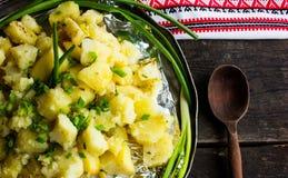 Aptitretande bakad potatis i aluminiumrundamaträtt med stekt kyckling och salladslök och inlagda gurkor och vitlök Royaltyfria Bilder