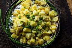 Aptitretande bakad potatis i aluminiumrundamaträtt med stekt kyckling och salladslök och inlagda gurkor och vitlök Arkivbild