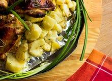 Aptitretande bakad potatis i aluminiumrundamaträtt med stekt kyckling och salladslök och inlagda gurkor och vitlök Royaltyfria Foton