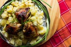 Aptitretande bakad potatis i aluminiumrundamaträtt med stekt kyckling och salladslök och inlagda gurkor och vitlök Arkivbilder