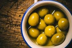 Aptitretande gräsplan saltade oliv på den gamla trätabellen Arkivfoto
