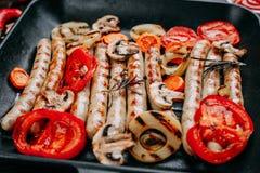 Aptitretande grillade korvar och grönsaker tjänade som i steka PA Royaltyfri Bild