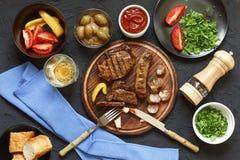 Aptitretande grillfestbiff på matställetabellen i en restaurang med nya grönsaker, oliv och vin italiensk tradition Arkivfoto
