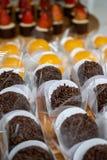 Aptitretande jordgubbe, kräm- och chokladgodis, en brasiliansk efterrätt som göras med ägg, och kokosnöt Quindim Brigadeiro - söt arkivfoton