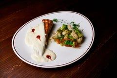 Aptitretande maträtt på en vit platta i händerna av flickauppassaren, mat arkivbild