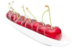 Aptitretande mogen körsbärsröd bärrad på lång olivgrön maträtt Arkivbild