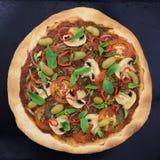 Aptitretande pizza med champinjoner, basilika och oliv på den svarta bakplåten Top beskådar Arkivbilder
