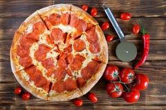 Aptitretande pizza med peperoni- och salamilögner på en träyttersida bredvid härliga tomater och röd peppar Picknick och grillfes royaltyfri foto