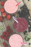 Aptitretande smoothies och detoxdrinkar från mogna bär Hallon jordgubbar, blåbär äta som är sunt royaltyfri foto