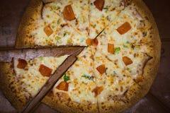 Aptitretande stort pizzasnitt in i stycken som ligger på brädet med nummer som indikerar dess diameter 16cm royaltyfri foto
