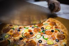 Aptitretande stort pizzasnitt in i stycken som ligger p? br?det med nummer som indikerar dess diameter 16cm royaltyfri foto