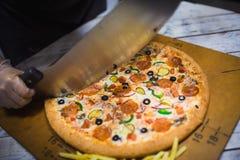 Aptitretande stort pizzasnitt in i stycken som ligger p? br?det med nummer som indikerar dess diameter 16cm royaltyfri fotografi