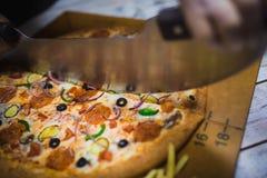 Aptitretande stort pizzasnitt in i stycken som ligger p? br?det med nummer som indikerar dess diameter 16cm royaltyfria foton