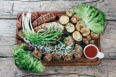 Aptitretande stycken för grillat griskött på gallret som framläggas på ett träbräde, tillsammans med sidor av grön sallad och pot royaltyfria foton