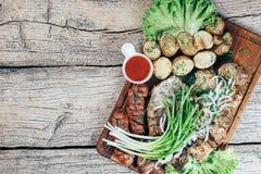 Aptitretande stycken för grillat griskött på gallret som framläggas på ett träbräde, tillsammans med sidor av grön sallad och pot royaltyfri fotografi