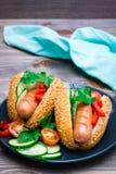 Aptitretande varmkorvar från stekte korvar, sesambullar och nya grönsaker på en platta royaltyfri fotografi