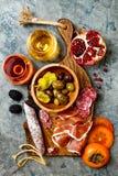 Aptitretare bordlägger med italienska antipastimellanmål och vin i exponeringsglas Charkuteribräde över grå färgbetongbakgrund To arkivbilder
