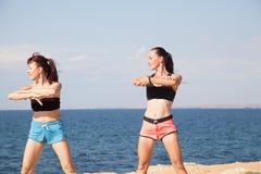 Aptitud de dos de las muchachas deportes del juego en la playa imágenes de archivo libres de regalías