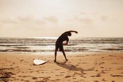Aptitud del hombre de la persona que practica surf en la playa Imágenes de archivo libres de regalías