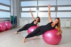 Aptitud, deporte, ejercitando la forma de vida - grupo de mujeres que hacen ejercicios con las bolas del ajuste en una clase de P Fotos de archivo