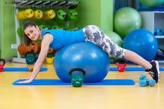 Aptitud, deporte, entrenamiento, gimnasio y concepto de la forma de vida - mujer joven que hace ejercicio en bola de la aptitud Imagen de archivo libre de regalías