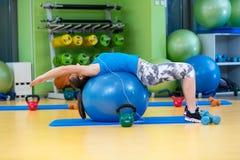 Aptitud, deporte, entrenamiento, gimnasio y concepto de la forma de vida - mujer joven que hace ejercicio en bola de la aptitud Foto de archivo