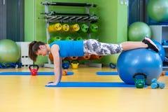 Aptitud, deporte, entrenamiento, gimnasio y concepto de la forma de vida - mujer joven que hace ejercicio en bola de la aptitud Fotografía de archivo libre de regalías