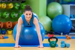 Aptitud, deporte, entrenamiento, gimnasio y concepto de la forma de vida - mujer joven que hace ejercicio en bola de la aptitud Fotografía de archivo