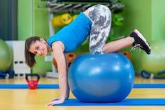 Aptitud, deporte, entrenamiento, gimnasio y concepto de la forma de vida - mujer joven que hace ejercicio en bola de la aptitud Fotos de archivo libres de regalías