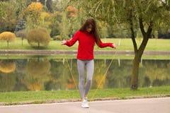 Aptitud, deporte, entrenamiento, parque y concepto de la forma de vida - mujer blanca sonriente que ejercita con la comba al aire Fotos de archivo