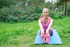 Aptitud, deporte, entrenamiento, parque y concepto de la forma de vida - mujer sonriente que hace ejercicios en la estera al aire Imágenes de archivo libres de regalías