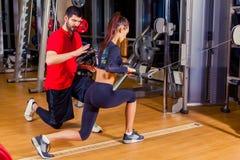 Aptitud, deporte, entrenamiento y concepto de la gente - mujer de ayuda del instructor personal que trabaja con en el gimnasio imagen de archivo