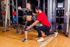 Aptitud, deporte, entrenamiento y concepto de la gente - mujer de ayuda del instructor personal que trabaja con en el gimnasio fotos de archivo libres de regalías