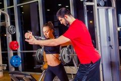 Aptitud, deporte, entrenamiento y concepto de la gente - mujer de ayuda del instructor personal que trabaja con en el gimnasio imágenes de archivo libres de regalías