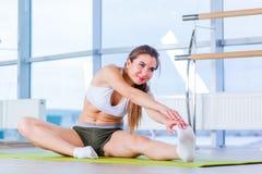Aptitud, deporte, entrenamiento y concepto de la gente - mujer joven feliz que estira antes de correr en gimnasio foto de archivo libre de regalías
