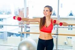 Aptitud, deporte, entrenamiento y concepto de la gente - mujer que ejercita con pesas de gimnasia Imagen de archivo libre de regalías