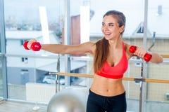 Aptitud, deporte, entrenamiento y concepto de la gente - mujer que ejercita con pesas de gimnasia Foto de archivo